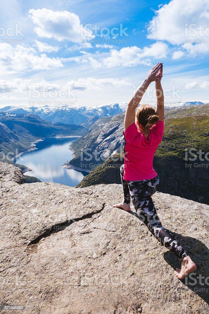 Young woman doing yoga on Trolltunga. Happy girl enjoy beautiful foto stock royalty-free