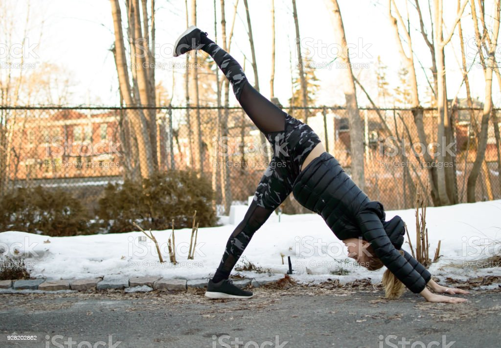 Young woman doing yoga outdoors in cold weather stock photo