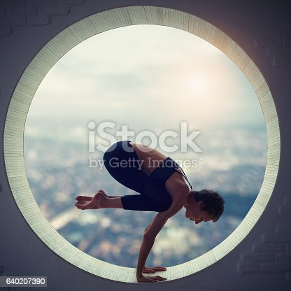 young woman doing bakasana in the round window