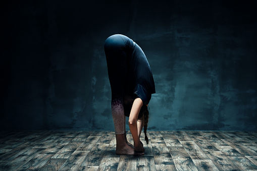 Young Woman Doing Yoga Standing Forward Bend Pose In Dark Room Stock Photo - Download Image Now