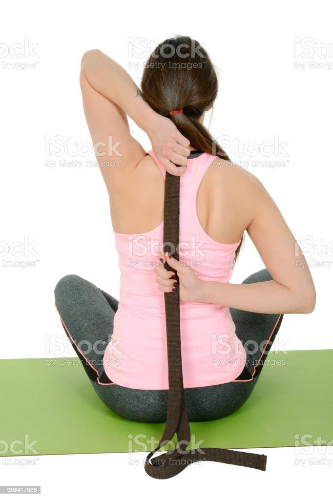 Młoda kobieta robi jogę za pomocą pasa jak rekwizyty - Zbiór zdjęć royalty-free (Joga)