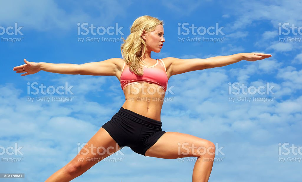 Young Woman Doing Yoga Warrior Pose stock photo