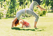 Young woman doing yoga with baby in the summer park.