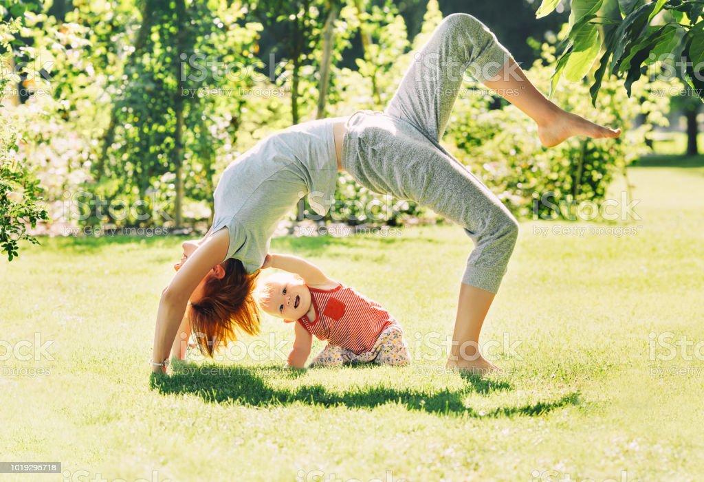 Mujer joven haciendo yoga con el bebé en el parque de verano. - foto de stock
