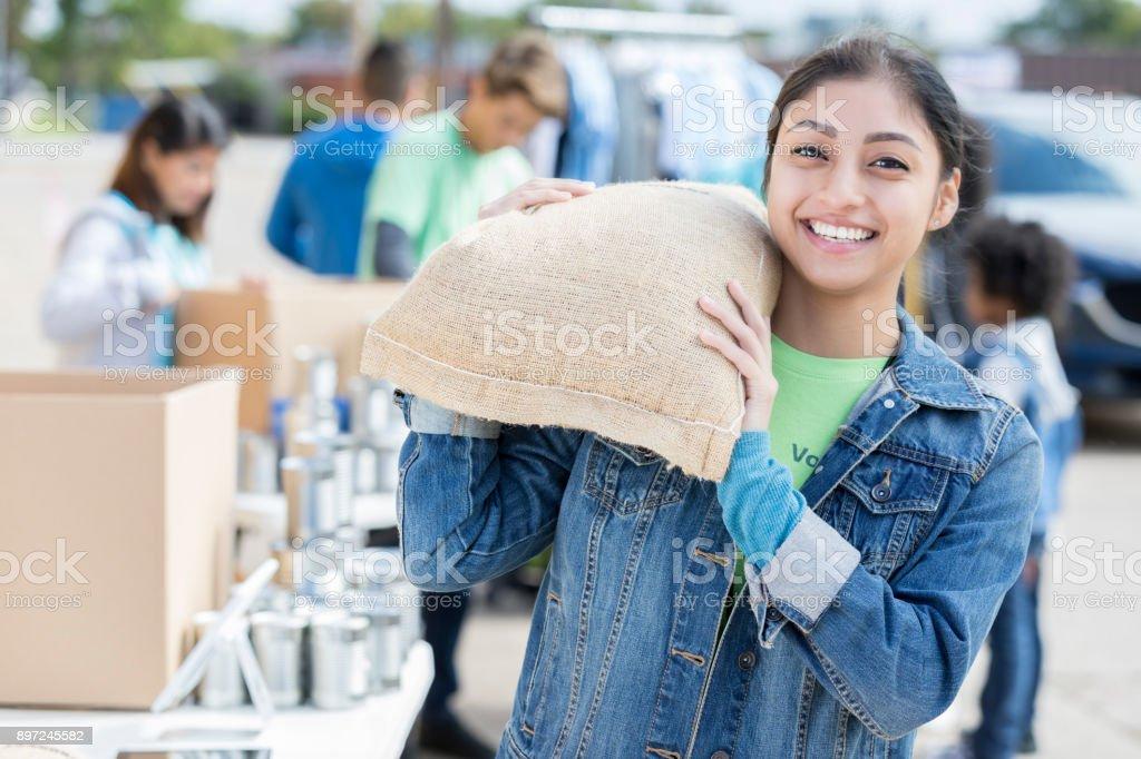 Mujer joven dona bolsa de alimentos durante la comida - foto de stock