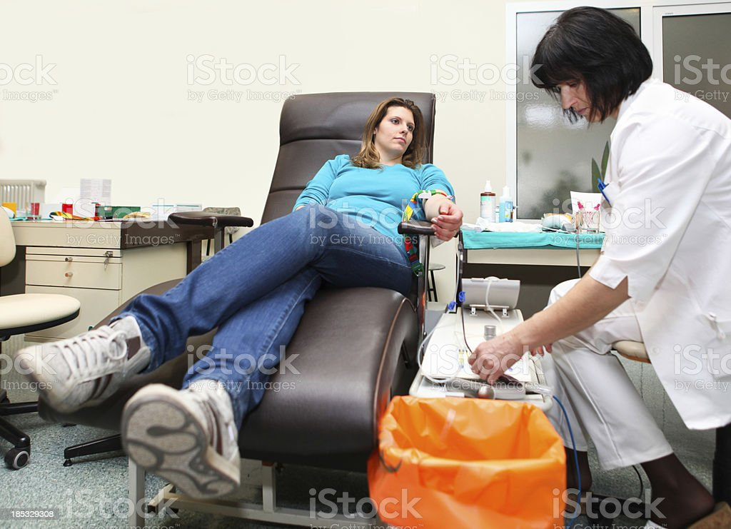 Young woman donating blood in a blood bank stock photo