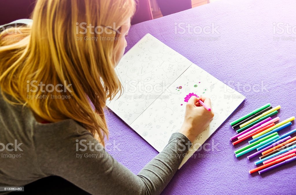 Young woman drawing adult coloring book at home stock photo