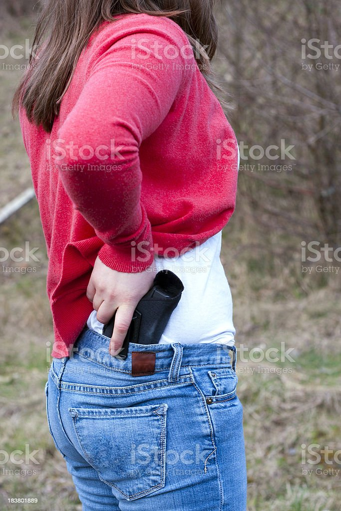 Young Woman Drawing From an Inside-the-Waistband Holster royalty-free stock photo