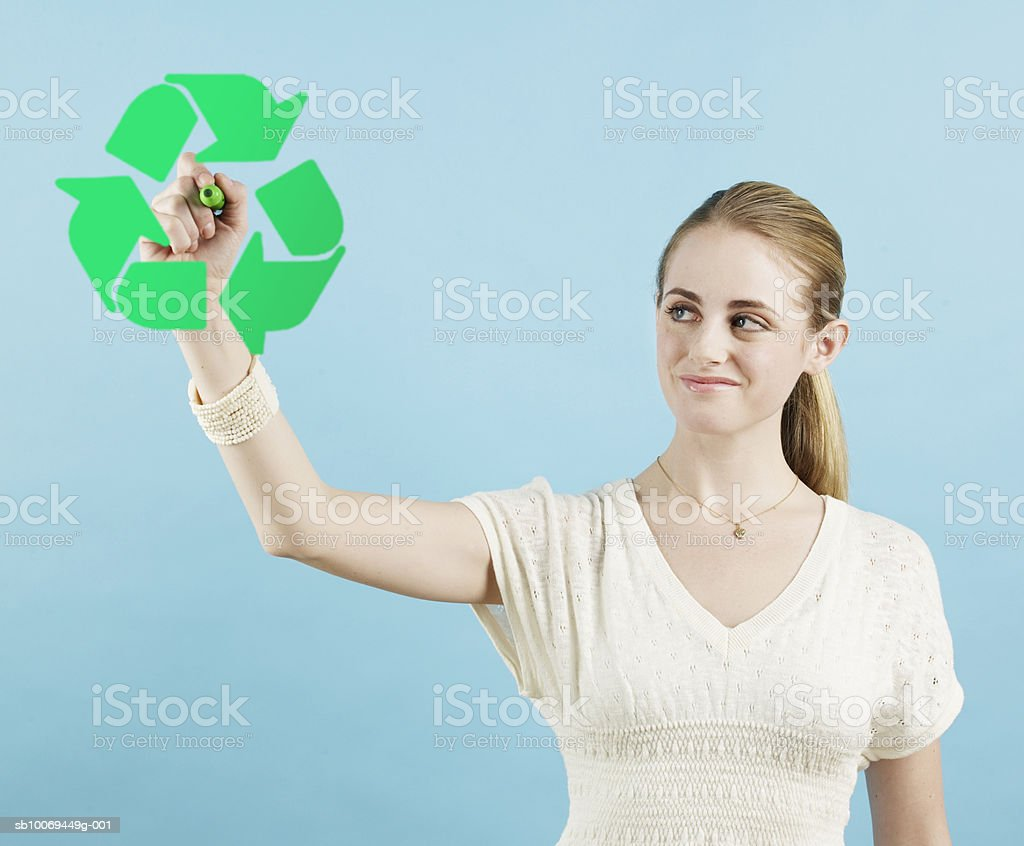 Young woman drawing green recycle sign, studio shot royalty-free stock photo