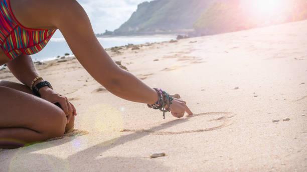junge frau zeichnung herzform im sand am strand, bali - armband water stock-fotos und bilder