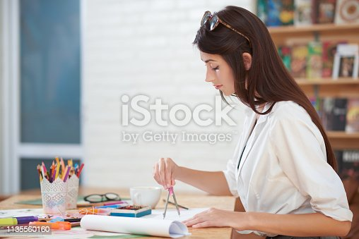 istock Young woman drawing with compasses in hand. 1135560160