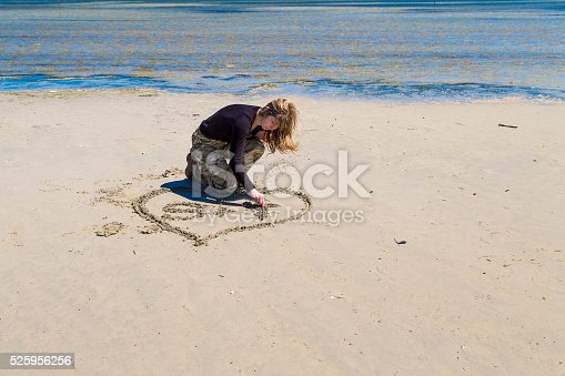 Young woman draws a heart in the sand, Grado, Italy