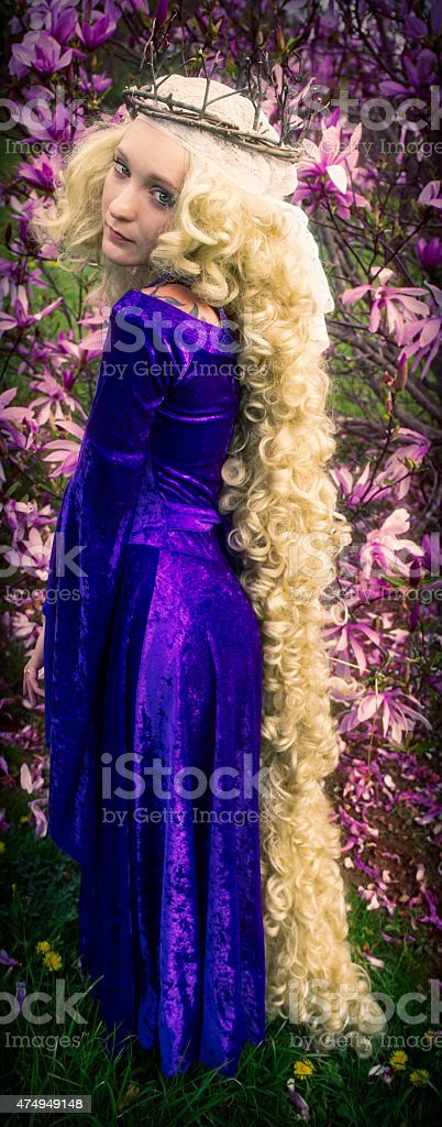 Young woman dressed like Rapunzel with long blond hair. stock photo