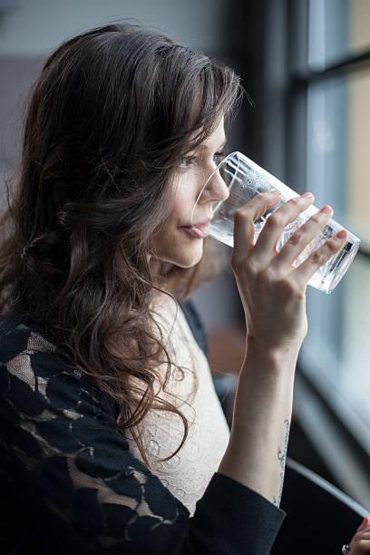 Junge Frau trinkt ein Glas Wasser in Glas mit Eis – Foto
