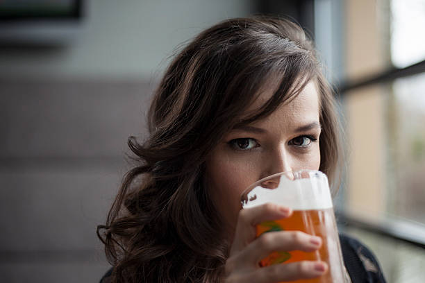 young woman drinking a pint glass of pale ale - beer alcohol stock pictures, royalty-free photos & images