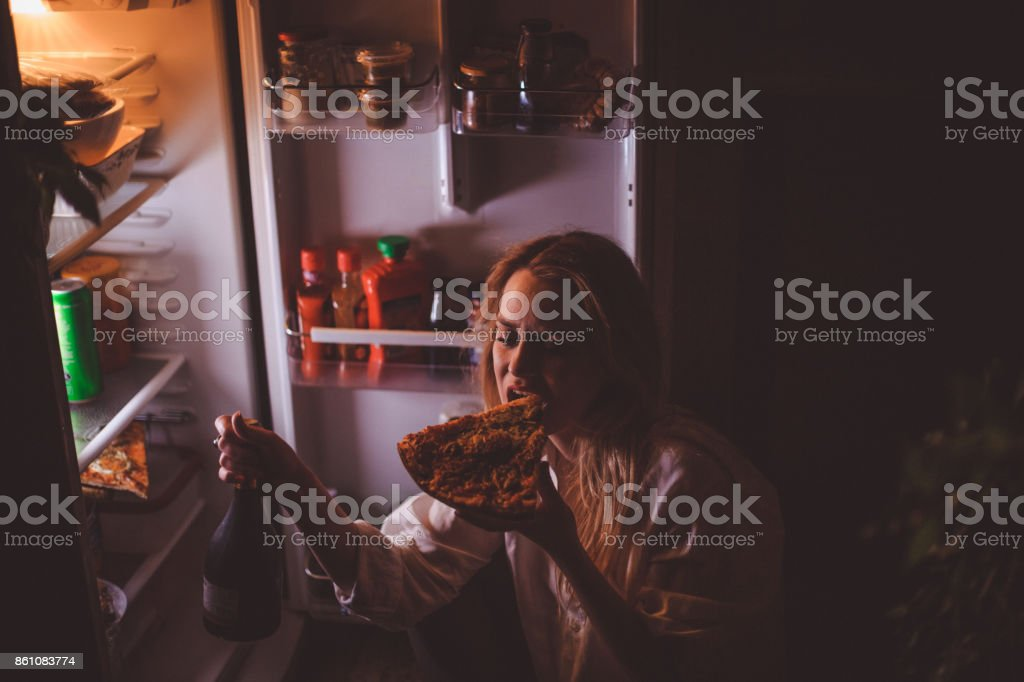 Young woman drinking and eating late night stock photo