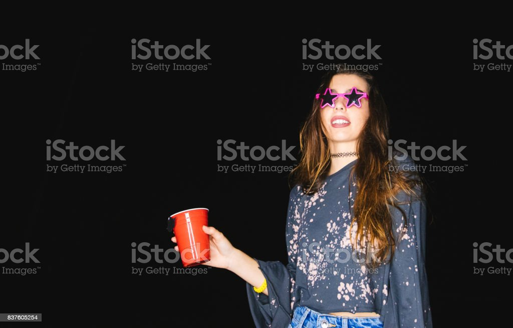 Young woman drinking and partying with funny sunglasses at night stock photo