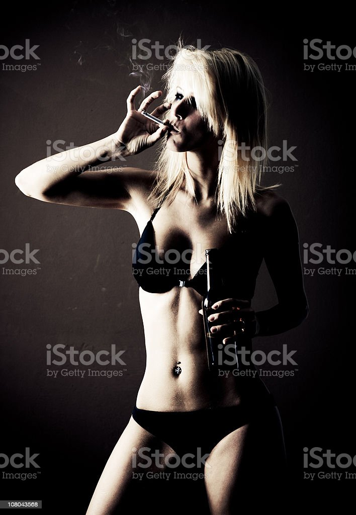 Young woman drinking and smoking stock photo