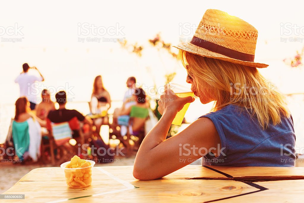 Young woman drinking beer in a beach bar stock photo