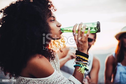 Young woman drinking beer at the beach party.