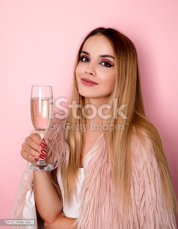 Young smiling woman holding glass with champagne