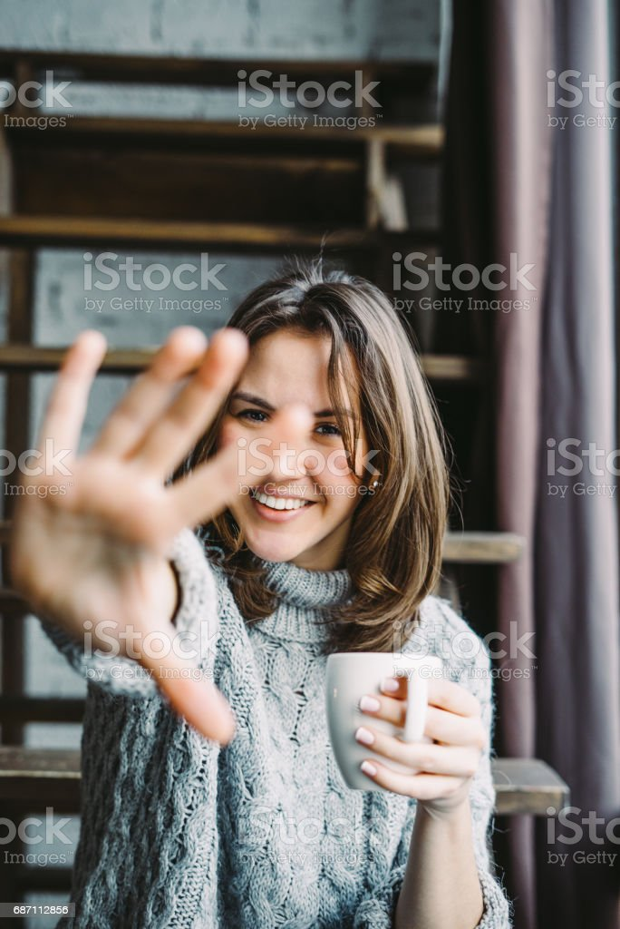 Young woman drinking coffee and hiding from the camera stock photo