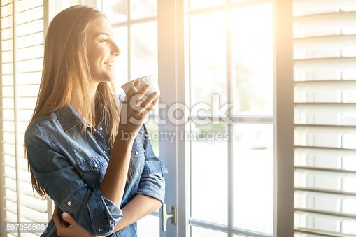 Cheerful young woman drinking coffee and looking through window. With long hair and denim shirt. Tall windows with shutters, sunbeam.