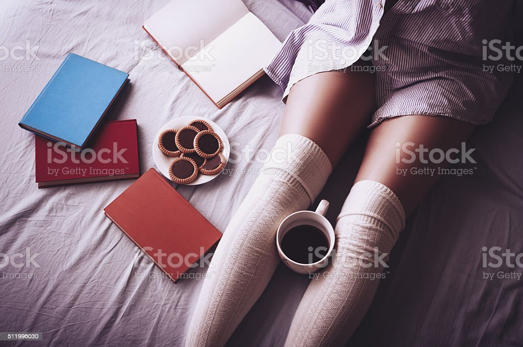Young woman drinking coffee and reading stock photo