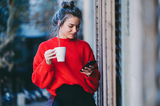 Young woman drinking coffee and texting