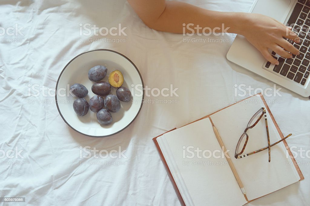 Young woman drinking coffee at home in her bed