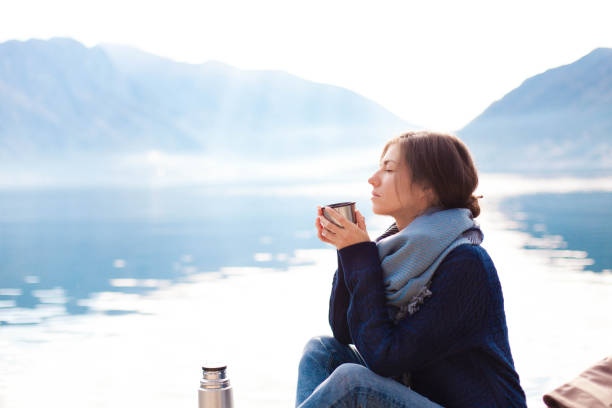 Young woman drinking coffee at sea beach. Cozy winter picnic by morning mountains stock photo