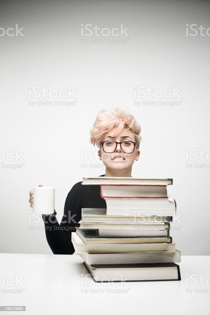 Young Woman Drinking Coffee Behind Pile of Textbooks royalty-free stock photo
