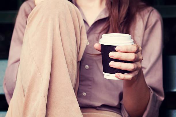 Junge Frau trinkt Kaffee von Wegwerfbecher – Foto