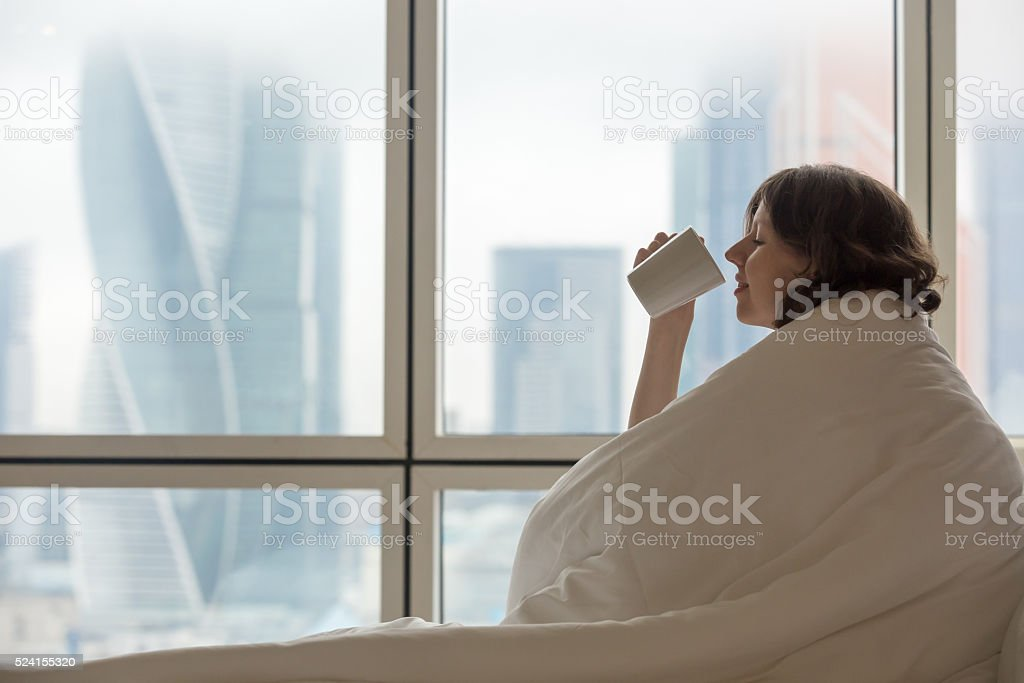 Young woman drinking coffee in bed stock photo