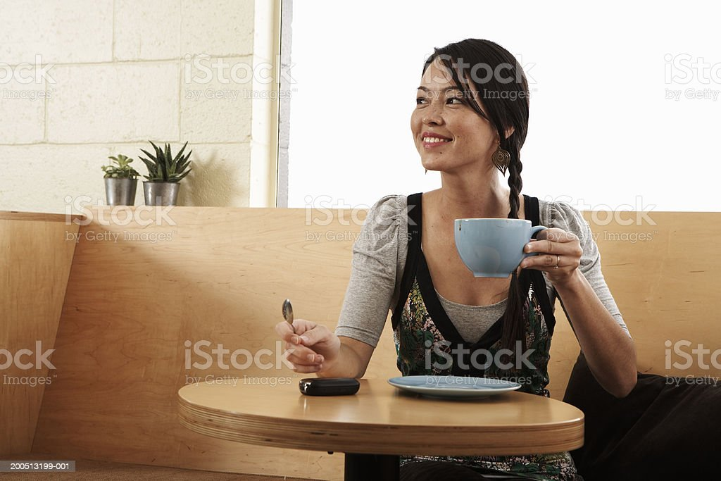 Young woman drinking coffee in cafe, looking away, smiling royalty-free stock photo