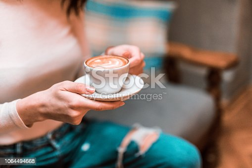 Close-up of young woman drinking coffee in a downtown café