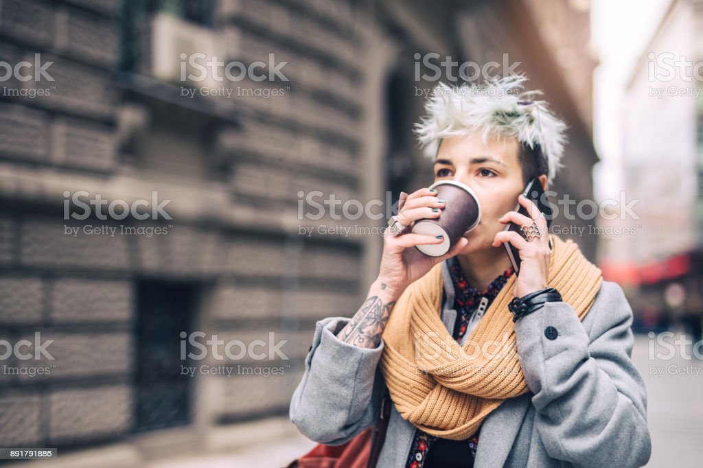 Young woman drinking coffee in the city stock photo