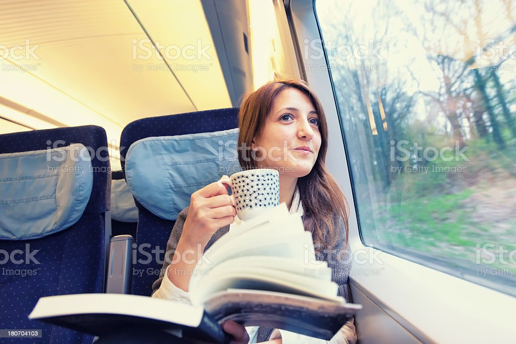 A young woman drinking coffee inside a running train stock photo