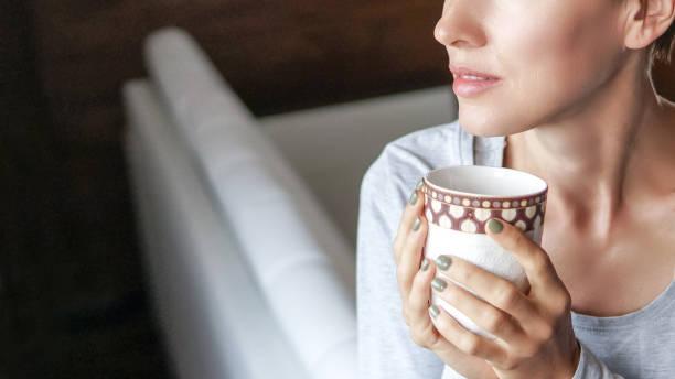 Mulher nova que bebe o café ou o chá com luz da manhã - foto de acervo
