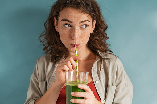 Beautiful woman drinking an organic green smoothie. Fit young woman drinking detox juice using paper straw isolated against blue background. Healthy girl enjoy detox drink and looking away.