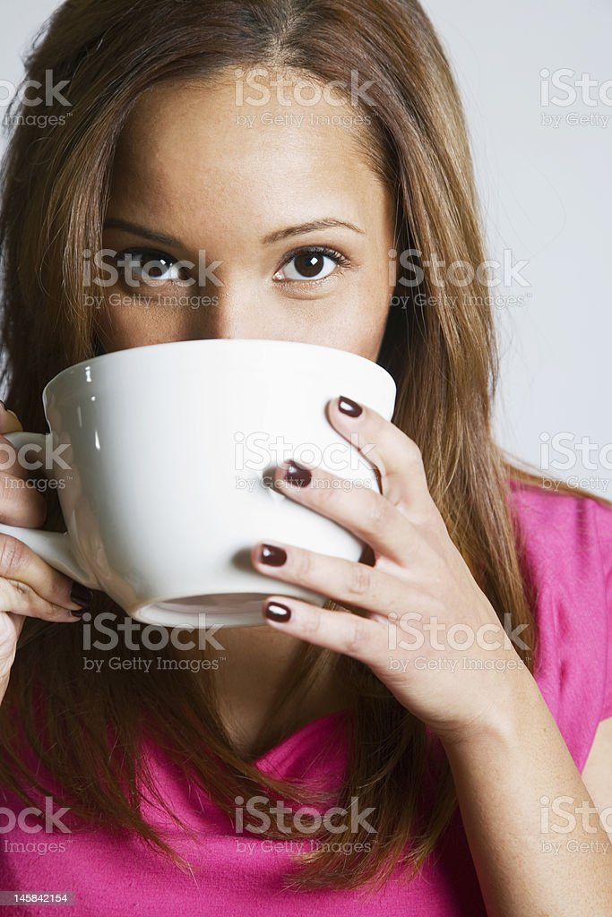 young woman drinking from an oversized cup royalty-free stock photo