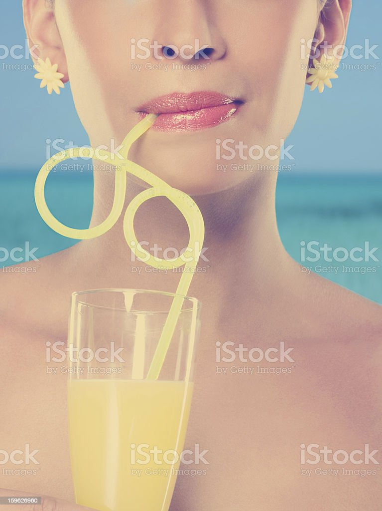 Young woman drinking glass of juice with curly straw stock photo