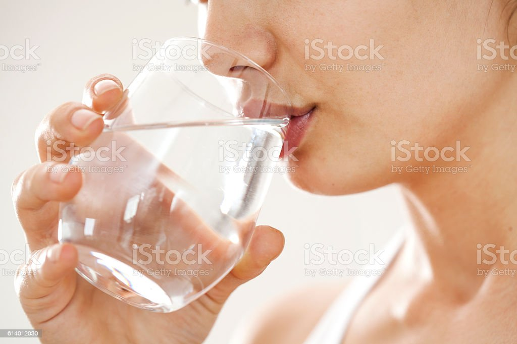 Young woman drinking  glass of water stock photo