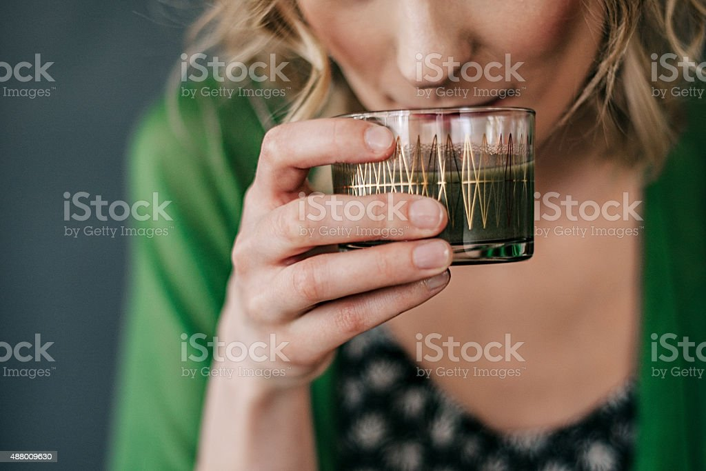 Young woman drinking green juice stock photo