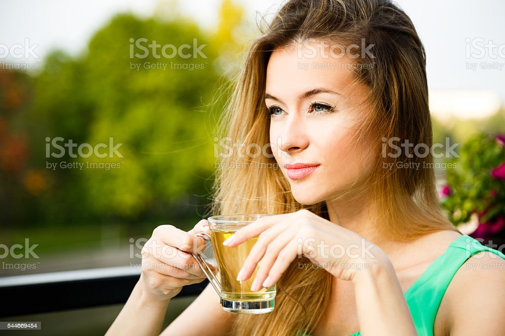 Young Woman Drinking Green Tea Outdoors stock photo