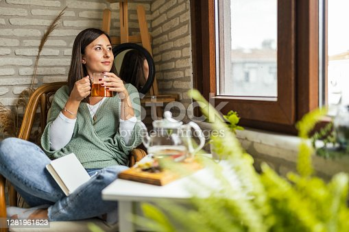 Young Woman drinking her winter tea and welcoming new day