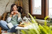 istock Young Woman drinking her winter tea and welcoming new day 1281961623
