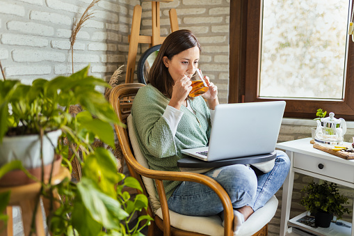 Young Woman drinking her winter tea while working at home