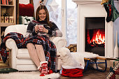 istock Young woman drinking hot chocolate by the fireplace 1175802654