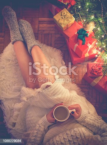 Young woman in a sweater enjoying a mug of hot coffee on Christmas night